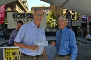 Peter Brockett receiving the cheque from Dick Smith